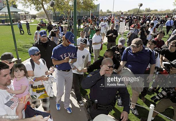 SURPRISE United States Texas Rangers rookie Yu Darvish signs autographs for fans after participating in the major league team's first official day of...