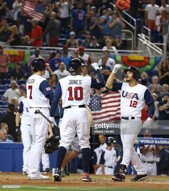 United States third baseman Nolan Arenado is congratulated by teammates Christian Yelich and Adam Jones after hitting a three-run home run during the...