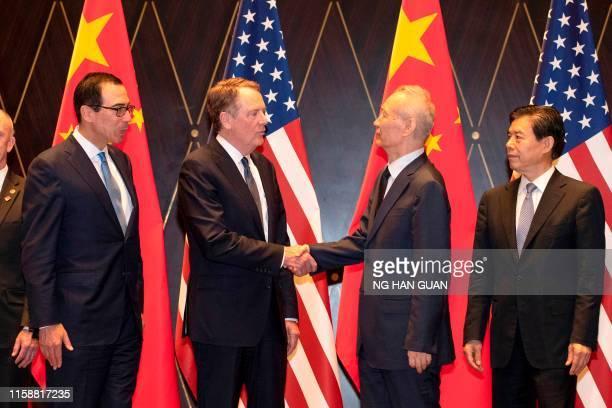 United States Trade Representative Robert Lighthizer shakes hands with China's Vice Premier Liu He as US Treasury Secretary Steven Mnuchin and...