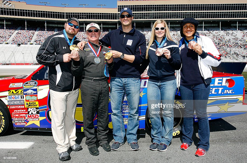 United States woman's bobsled driver Erin Pac (2R), stands along side team brakeman Elana Meyers (R), NASCAR driver Geoff Bodine (2L), head of the Bodine bobsled project, men's bobsled team pilot Steve Holcomb (L) and pushman Steve Mesler (C) on the grid prior to the NASCAR Camping World Truck Series E-Z-GO 200 at Atlanta Motor Speedway on March 6, 2010 in Hampton, Georgia.