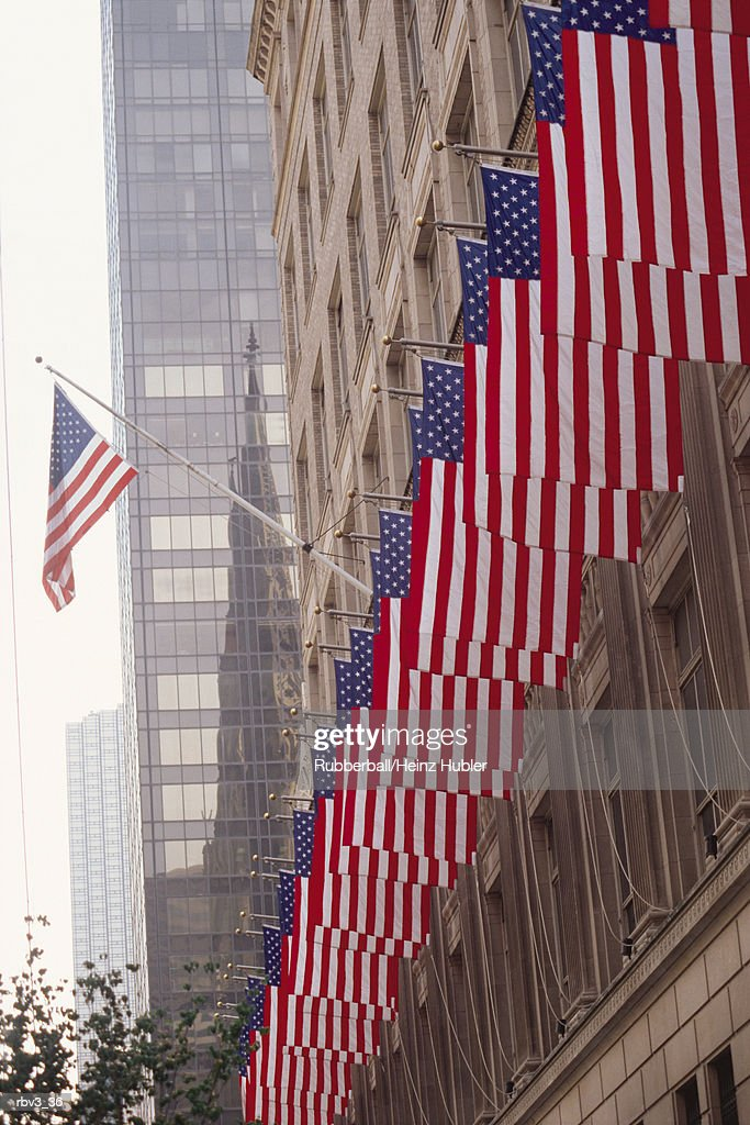 United States_ flags run the length of a brown stucco building as one looks up to see a black windowed skyscraper rise to the sky : Foto de stock