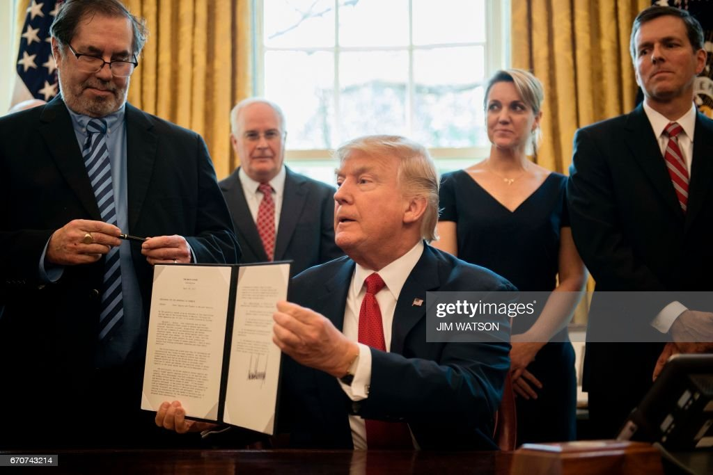 United Steelworkers Union International President Leo W. Gerard (L) looks at the pen after US President Donald Trump (C) signed the Memorandum Regarding the Investigation Pursuant to Section 232(B) of the Trade Expansion Act at the White House in Washington, DC, April 20, 2017. /