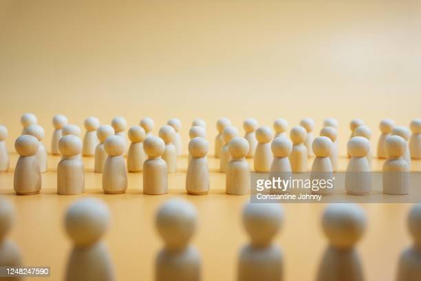 united. wooden figurines standing together to face authority. - democracy stock pictures, royalty-free photos & images