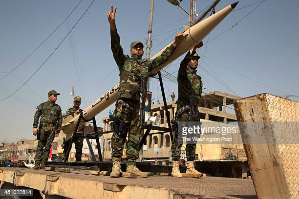 Units of Moqtada Sadr's militia stand with what appears to be a truck mounted missile as they parade down a main street of the Shi'a stronghold of...