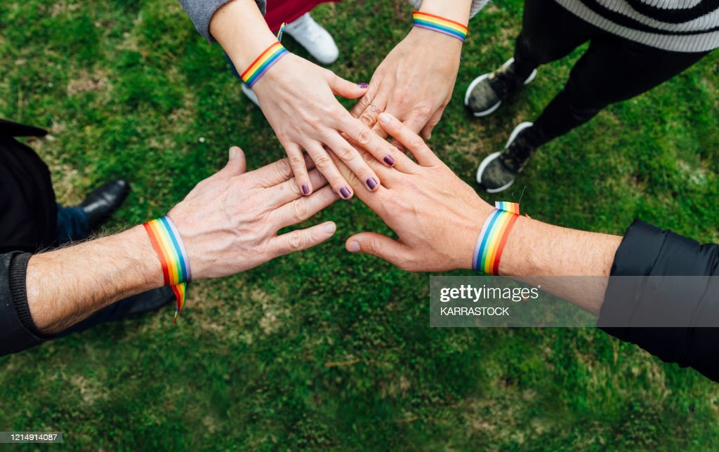 Unity hands of diverse people with multicolored bracelet : Stock Photo