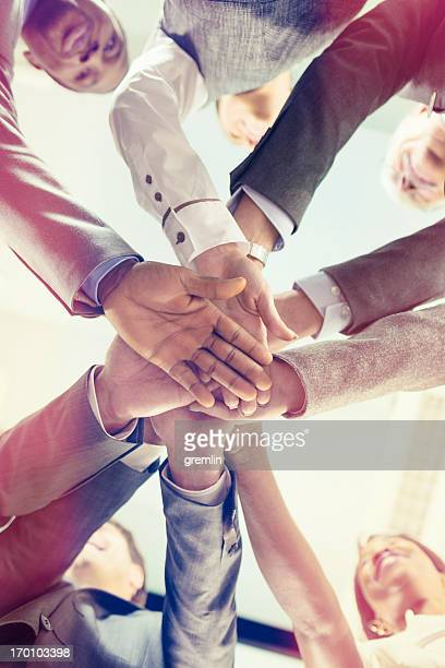 Unity of successful multi-ethnic business people holding hands