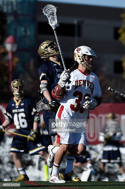 Univeristy of Denver's Zach Miller makes the gamewinning goal on Notre Dame's Sahne Doss during the Pioneers' 1110 win The University of Denver...