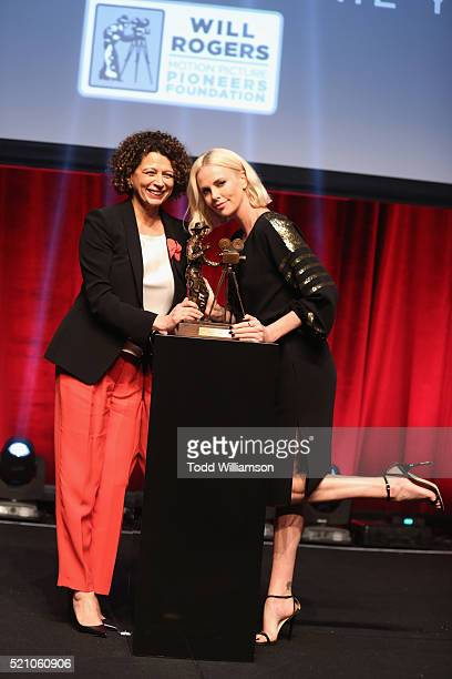 """Universal Pictures Chairman Donna Langley and actress Charlize Theron speak onstage during the 2016 Will Rogers """"Pioneer of the Year"""" Dinner Honoring..."""