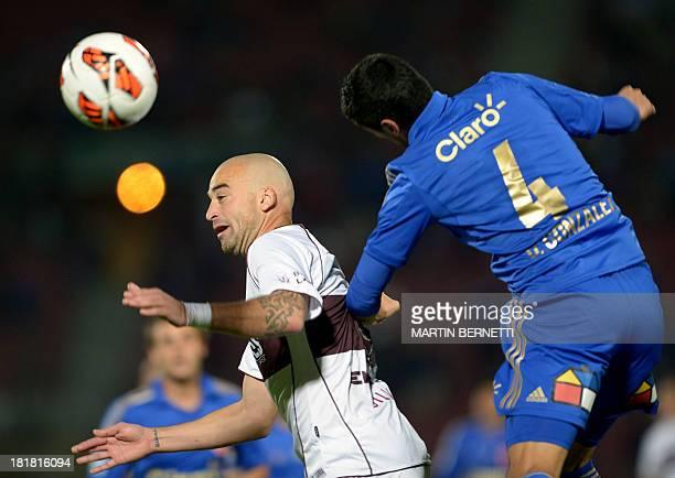 Universidad de Chile footballer Osvaldo Gonzalez jumps for a header with Santiago Silva, of Argentina's Lanus, during their Copa Sudamericana 2013...