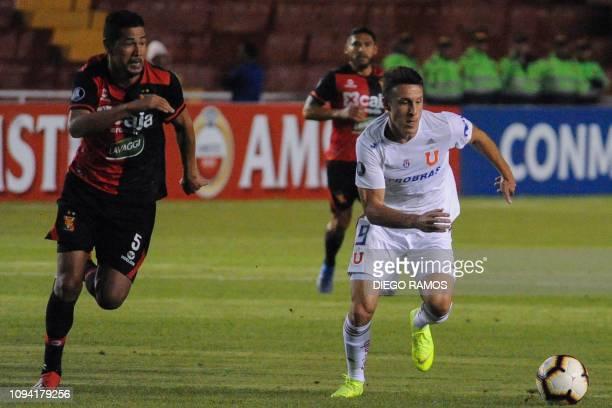 Universidad de Chile player Angelo Henriquez vies for the ball with Peru's Melgar player David Villaba during their Copa Libertadores game at the...