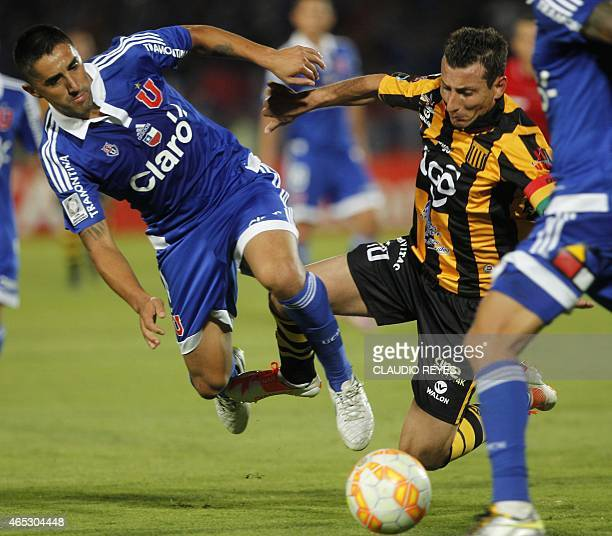 Universidad de Chile's footballer Osvaldo Gonzalez vies for the ball with Bolivia's The Strongest's Pablo Escobar during their Copa Libertadores...