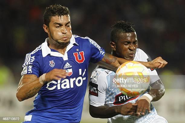 Universidad de Chile's footballer Paulo Magalhaes vies for the ball with Ecuador's Emelec's Miller Bolanos during the Copa Libertadores football...