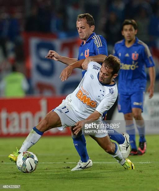 Universidad de Chile's Gustavo Lorenzetti vies for the ball with Brazil's Cruzeiro's Everton Riveiro during their Copa Libertadores 2014 football...