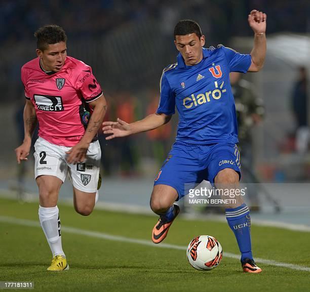 Universidad of Chile footballer Isac Diaz vies for the ball with Independiente of Ecuador Mario Pineida during their Copa Sudamericana 2013 football...