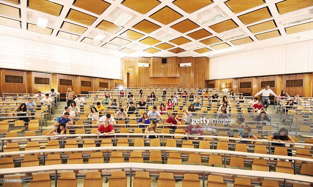 University amphitheatre full of students doing exam. : Stock Photo