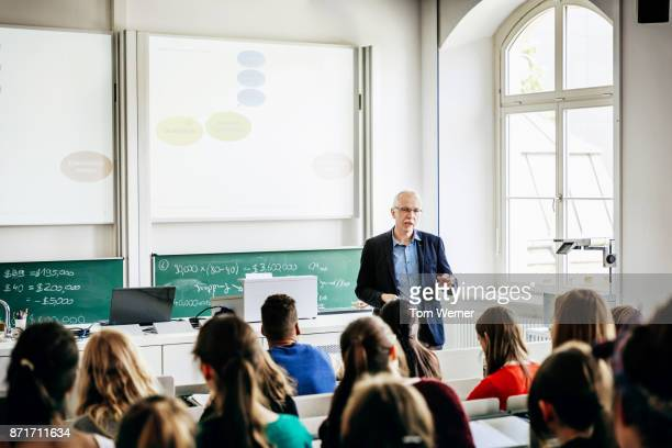 university lecturer addressing his students - college professor stock-fotos und bilder