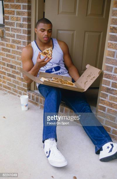 University of Auburn's Center Charles Barkley sits on his doorstep and eats a slice of pizza in a circa 1980s photo