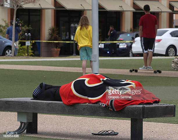 A University of Central Florida student who was evacuated from her dorm building background left lays on a bench Monday March 18 in Orlando after...