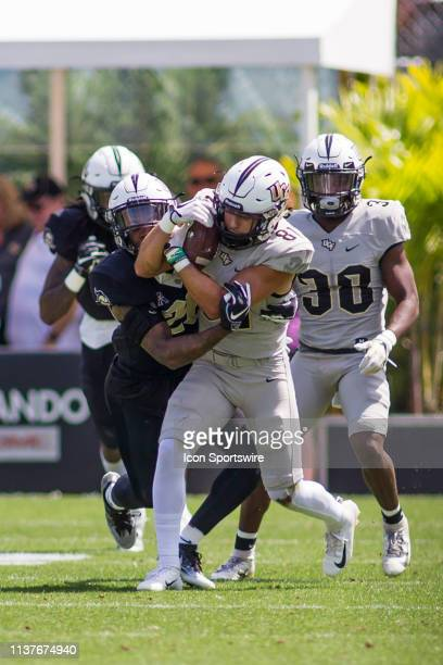 University of Central Florida wide receiver Alex Harris catches a pass as he is tackled by defensive back Brandon Moore in the UCF Football Spring...