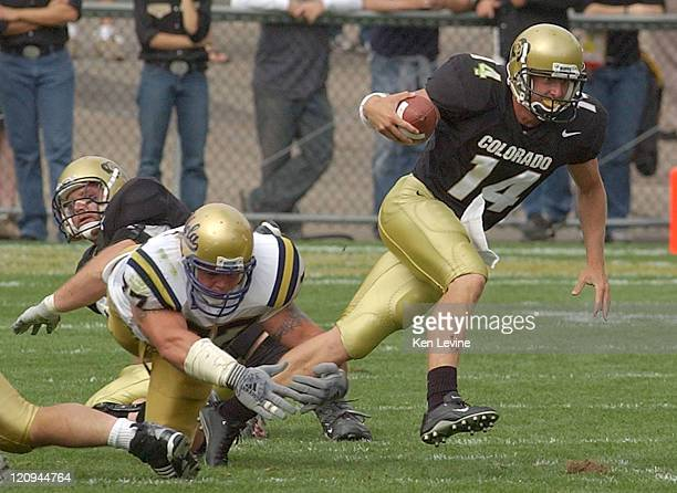 University of Colorado quarterback Joel Klatt eludes the tackle of UCLA defensive tackle Rodney Leisle during the third quarter Saturday Sept 6 2003...