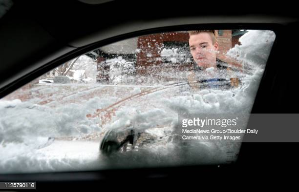 University of Colorado senior Jack Brittingham uses a lacrosse stick to scrape snow off the windows of his car on Monday in Boulder