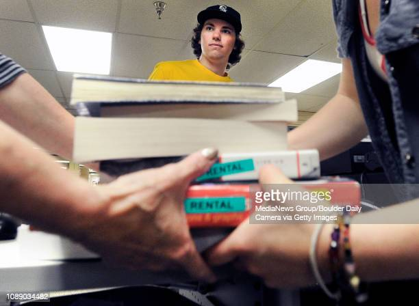 University of Colorado sophomore Evan Michalec watches as employees Kerrie Summerhays left and Justice Cook carry away his textbooks after selling...
