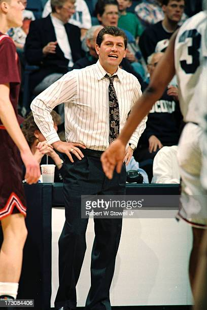 University of Connecticut basketball coach Geno Auriemma stand with his hands on his hips on the sideline during a game Storrs Connecticut 1994