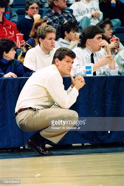 University of Connecticut coach Geno Auriemma watches the action while crouched on the sideline Gampel Pavilion Storrs CT 1991