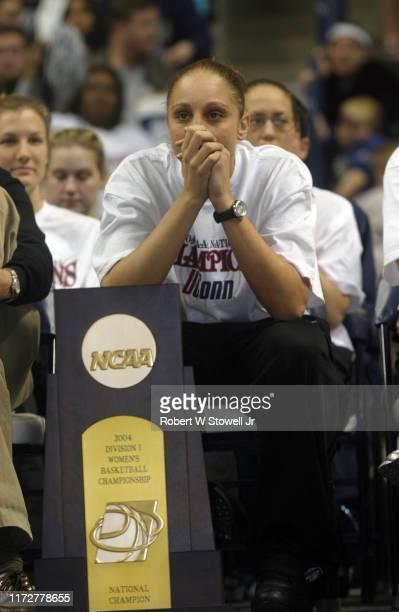 University of Connecticut NCAA women's basketball player of year Diana Taurasi sits her team's the third consecutive national championship trophy...