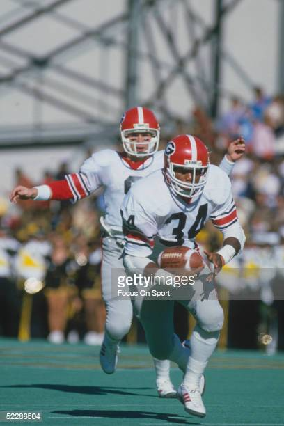 University of Georgia's running back Herschel Walker runs with the ball during a game circa 1980-1982. Herschel Walker was elected to the College...