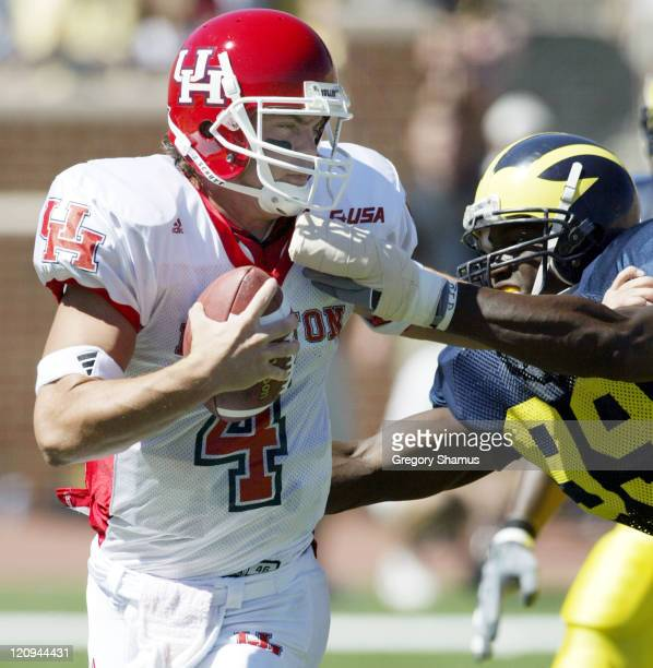 University of Houston QB Kevin Kolb tries to get away from University of Michigan DL Pierre Woods during 1th quarter action at Michigan Stadium in...