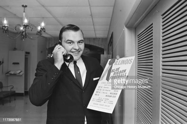 University of Illinois All-American linebacker Dick Butkus speaks with friends on the phone while on a poster tour at the Illini Club Luncheon,...