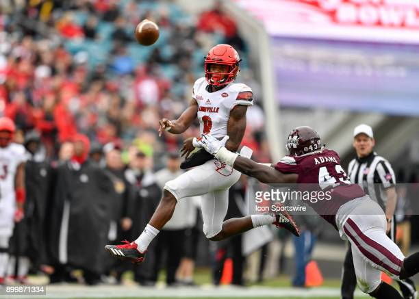 University of Louisville Cardinals quarterback Lamar Jackson throws a pass on the run before being hit by Mississippi State defensive end Fletcher...