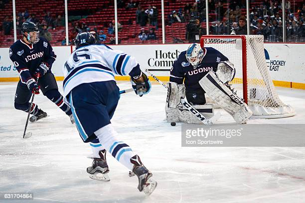 University of Maine Black Bears forward Dane Gibson's shot on goal is bounced off of UC onn Huskies goaltender Adam Huska's pad during the third...