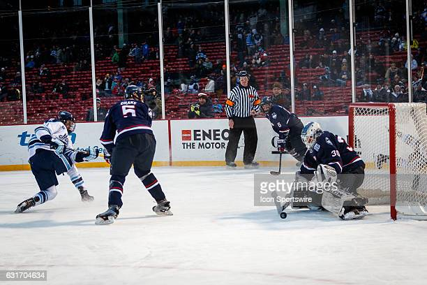University of Maine Black Bears forward Mitchell Fossier fires a shot at UConn Huskies goaltender Adam Huska during the third period of the game...