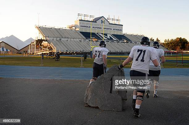 University of Maine football player touch the rock at the entrance to the Harold Alfond Sports Stadium in Orono just before practice Wednesday,...