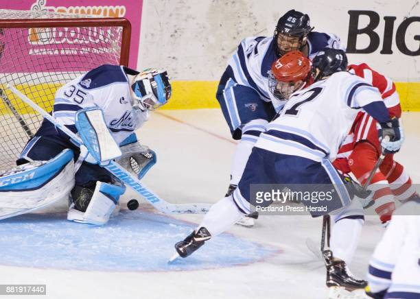 University of Maine goalie Rob McGovern get in front of the puck shot by Boston Universitys Brady Tkachuk who is surrounded by Maine defensemen Brady...