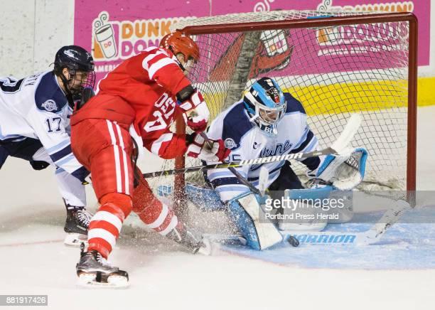 University of Maine goalie Rob McGovern gets a stick in front of Boston Universitys Brady Tkachuks shot who is followed by Maine defenseman Dante...
