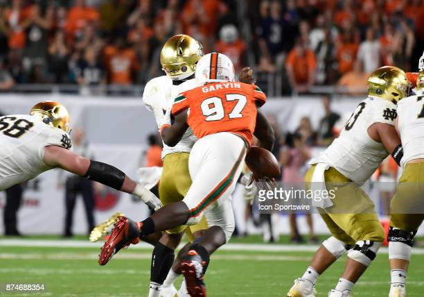 University of Miami defensive lineman Jonathan Garvin strips the ball from Notre Dame quarterback Brandon Wimbush during an NCAA football game...