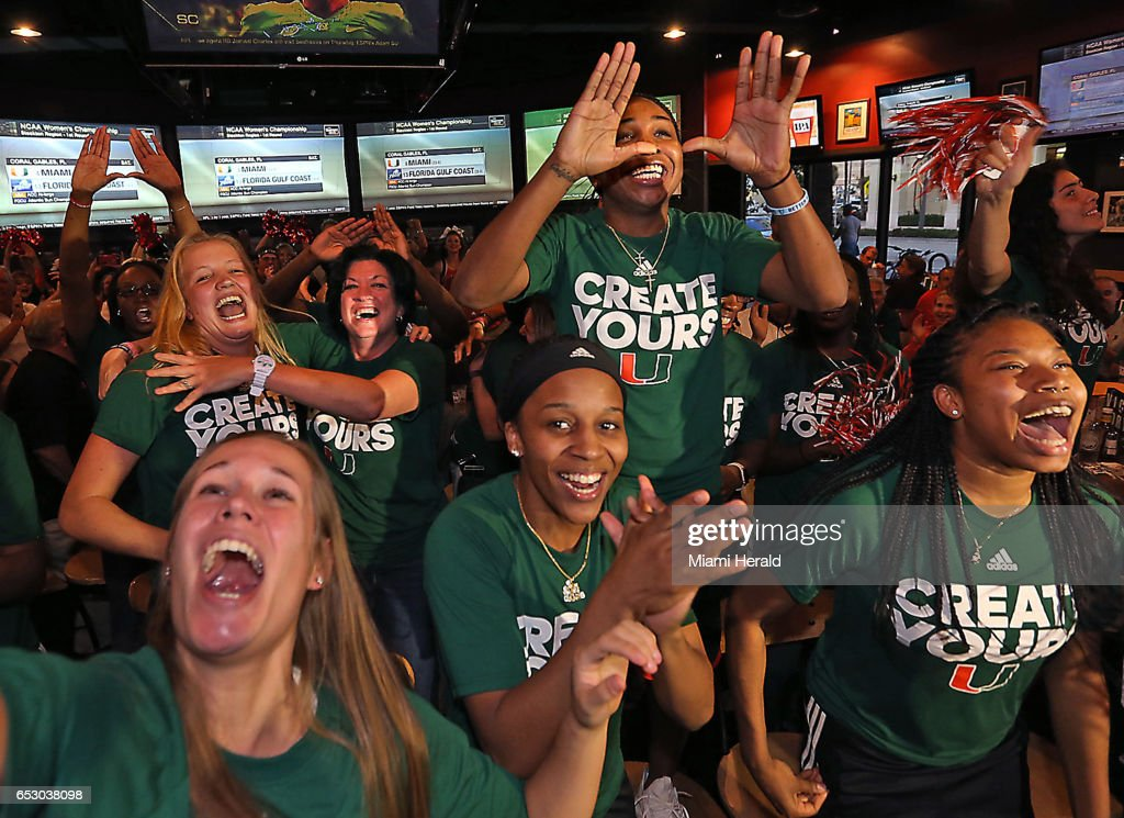 University of Miami head basketball coach Katie Meier, background, gets a hug from player Emese Hof as Jessica Thomas jumps up on a chair and throws up the U on Monday, March 13, 2017 as the team realizes it will be playing at home in the NCAA women's basketball tournament.