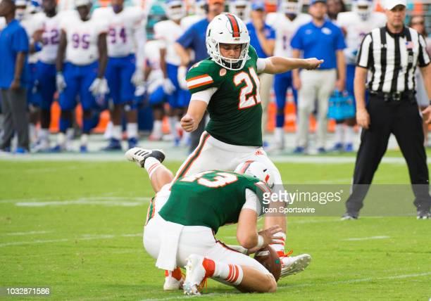 University of Miami Hurricanes Punter Jack Spicer holds the ball as University of Miami Hurricanes Kicker Bubba Baxa kicks an extra point during the...