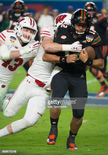 University of Miami Hurricanes Quarterback Malik Rosier runs with the ball and is tackled by Wisconsin Badgers Linebacker Andrew Van Ginkel along...