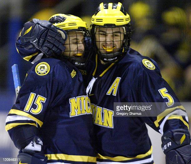 University of Michigan forward Jeff Tambellini is congratulated by teammate Brandon Rogers after scoring the winning goal against Ferris State during...