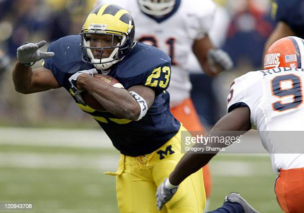 University of Michigan RB Chris Perry gets past Illinois DE Lee Robinson during first quarter action at Michigan Stadium on October 18 2003 Michigan...