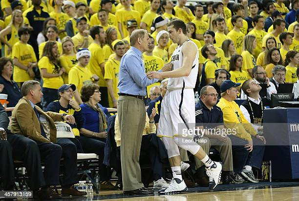 University of Michigan Wolverines head basketball coach John Beilein talks with Nik Stauskas during the game against the Houston Baptist Huskies at...