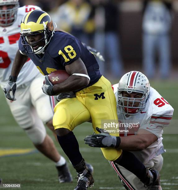 University of Michigan's Antonio Bass tries to escape the tackle of Ohio State University's Quinn Pitcock during fourth quarter action at Michigan...