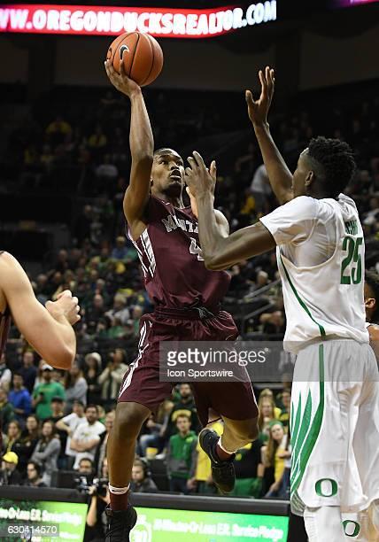 University of Montana freshman guard Sayeed Pridgett shoots over University of Oregon senior forward Chris Boucher during a nonconference NCAA...