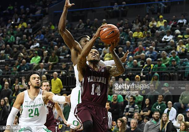 University of Montana redshirtsophomore guard Ahmaad Rorie goes in for a shot while defended by University of Oregon guard Dylan Ennis and University...