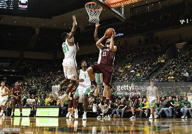 University of Montana senior forward Jack Lopez attempts to shoot while defended by University of Oregon guard Dylan Ennis during a nonconference...