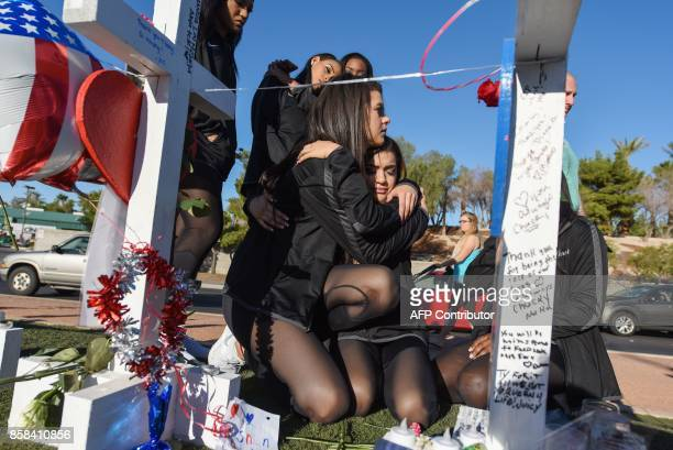 University of Nevada Las Vegas cheering squad member Gala Hernandez grieving for a friend killed in Sunday night's mass shooting is comforted by a...